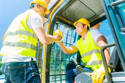 Two Asian workers in protective vests standing on construction m