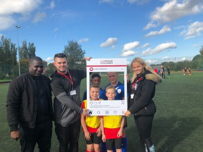 Bruce Dyer with Sport students Joshua Barker and Charlotte Howe and primary school pupils.