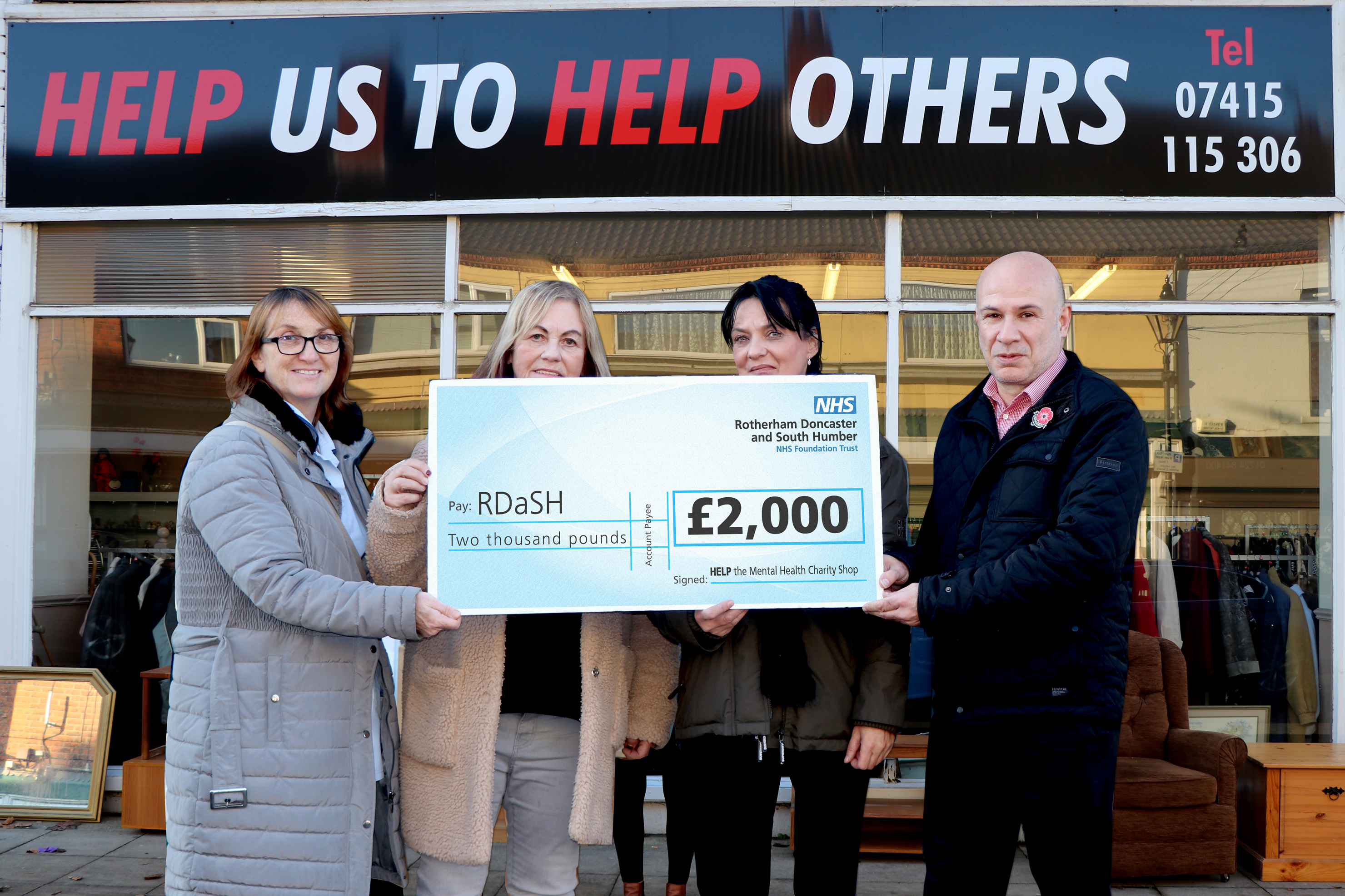 Volunteers and RDaSH staff are pictured with the cheque outside the charity shop