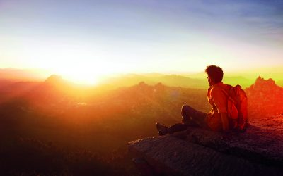 man-sitting-on-edge-facing-sunset-915972